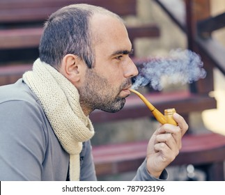 Man with a smoking pipe. Bearded handsome young man holding a smoking pipe