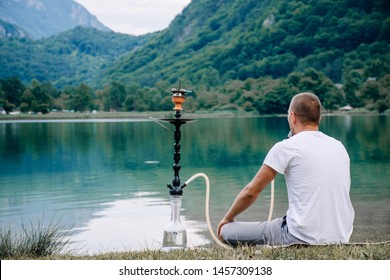 Man smoking shesha nargile near the lake alone