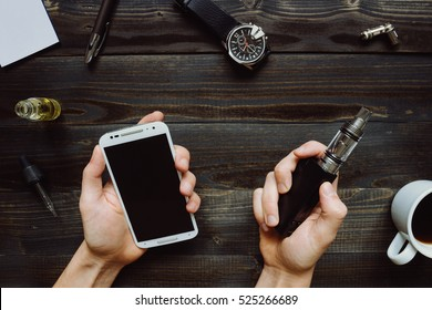 Man smoking vape or electronic cigarette and using smartphone. View from above. Vaping set, watch, coffee on the wooden background. Hipster or bussinesman style.