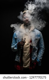 Man smoking or vaping e-cig or electronic cigarette holding a mod with a lot of clouds
