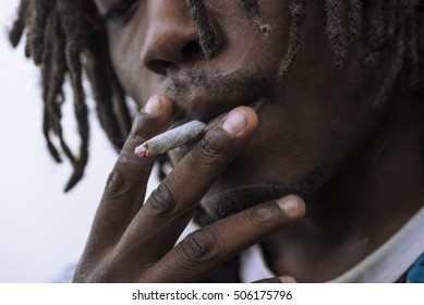 Man smoking a white paper joint close up.