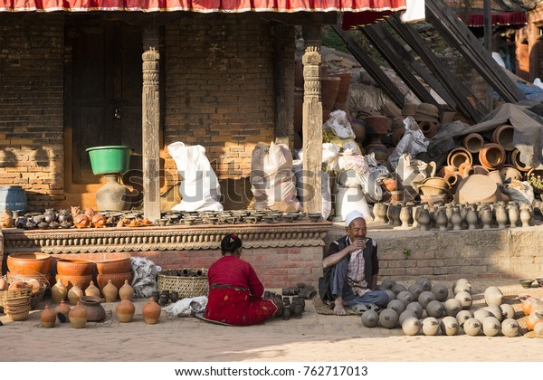 Man smoking and woman sitting among pots in front of shop in Potters Square, Bhaktapur, Nepal, November 21, 2017