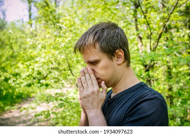 A man sneezes in a grove. Allergy concept