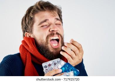man sneezes pills on a light background, flu, health, treatment, folk medicine
