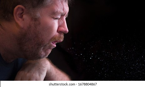 A man sneezes and releases droplets in the air