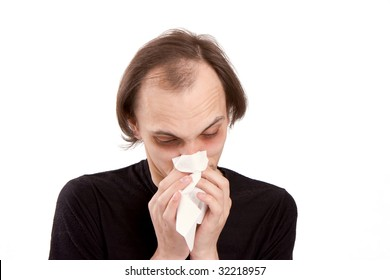 The man sneezes in a white paper handkerchief