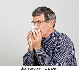 Man with a sneezing into handkerchief. Neutral gray background.