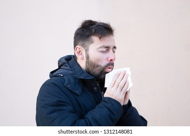 Man sneezing in winter with hanky in hand