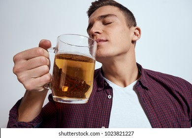 a man sniffs beer on a light background, alcohol