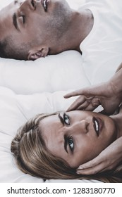 Man snoring in bed while his wife is covering ears. Medical health problem.