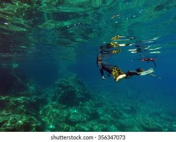 A man snorkeling along in the greenish water of the coastal of peninsular Malaysia