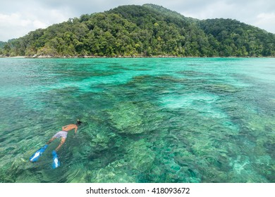 Man snorkeling in tropical island paradise of Ko Surin with emerald green water and coral reef, Thailand