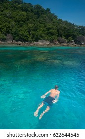 Man snorkeling in tropical island paradise of Ko Surin with emerald green water and coral reef, on Mu Koh Surin National Park, Phangnga, Thailand