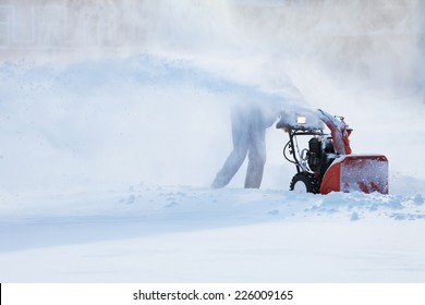 man with a snow blowing machine working in winter day
