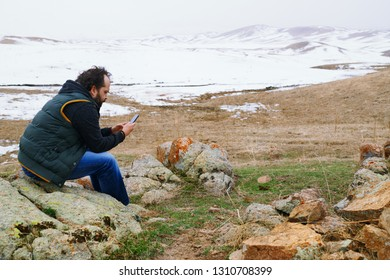 Man in snow landscape using GPS on his smartphone