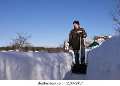 Man with a snow shovel in winter garden