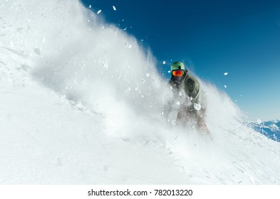 man snowboarder is going very fast freeride in the stream of snow avalanche