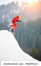 Man snowboarder jumping from the top of the snowy hill with snowboard at winter ski resort. Skiing and snowboarding concept
