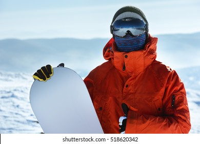 Man snowboarder stands with snowboard. Closeup portrait. Red jacket