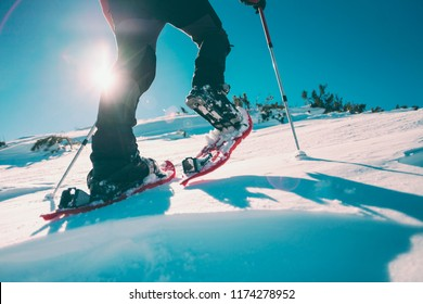 Man in snowshoes with trekking poles. Equipment for walking on snow close up. Journey through the mountains in winter. Shoes for travel. Men's legs.