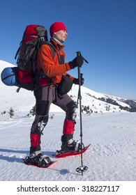 The man in snowshoes and with trekking poles is in the mountains.