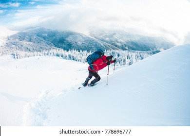 A man in snowshoes and trekking sticks in the mountains. Winter trip. Climbing of a climber against a beautiful sky with clouds. Active lifestyle. Climbing the mountain through the snow.