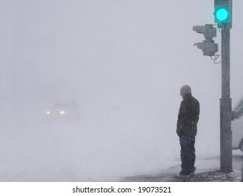 man in snowstorm stands on pedestrian crossing