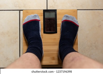 Man with socks standing on a scale and want to lose weight