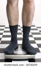 Man in socks standing on scale with on checkered floor that is slightly burned out in background