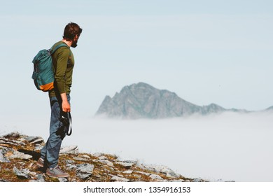 Man solo traveling in mountains adventure vacations freedom lifestyle outdoor with backpack and photo camera