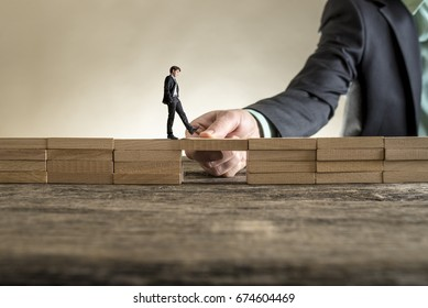 Man solving problems by building bridge with wooden block to span a gap for little businessman walking across.