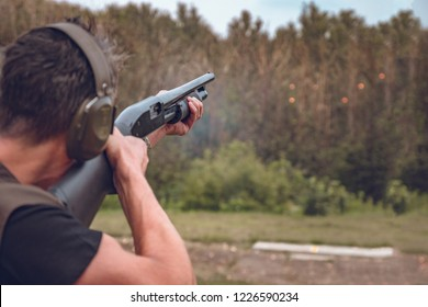 man in soundproof headphones shoots a hard disk at flying plates