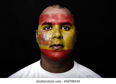 Man with Spain flag painted on her face on black background
