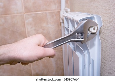 A man with a spanner mends  heater