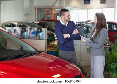 Man speaking to a businesswoman in a garage
