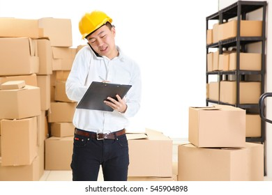 Man speaking by cellphone and holding clipboard at warehouse