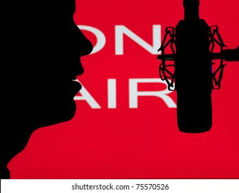 man speaking into the microphone with on the air sign in the background,for entertainment,broadcasting,sound themes