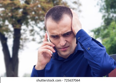Man, speaking, on the phone, scared, upset, looking down, in a blue shirt, emotion, excitement