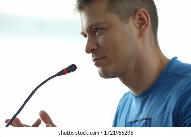 Der Mensch spricht vor dem Mikrofon, informelles Treffen. Speaker präsentiert Material auf Seminar oder Training. Technische Workshops erfolgreich durchführen. Lebendiges Business-Ambiente während der Ausbildung