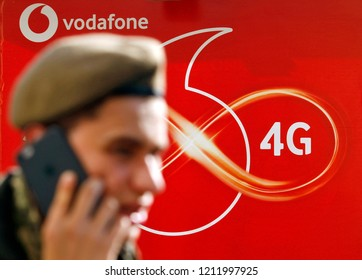 A man speaks on a mobile phone on street in front to a logo of 4G of Vodafone , British multinational telecommunications company, in Kiev, Ukraine, on 18 October 2018.