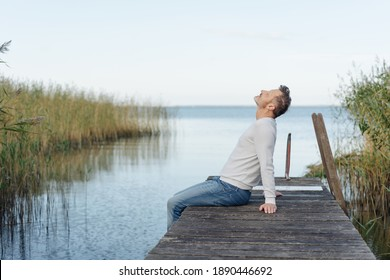 Man spending a relaxing day at the coast sitting on the edge of a wooden jetty with his head back unwinding
