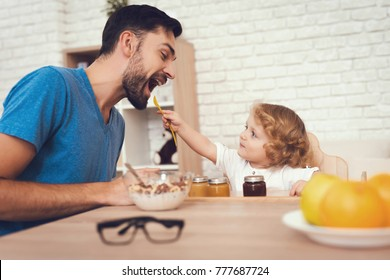A man spends time with his son. The father of boy is engaged in raising child. Baby is feeding his father. The boy is having breakfast with his father.