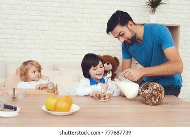 A man spends time with his sons. The father of two boys is engaged in raising children. Father feeds his son. Children have breakfast with their father.
