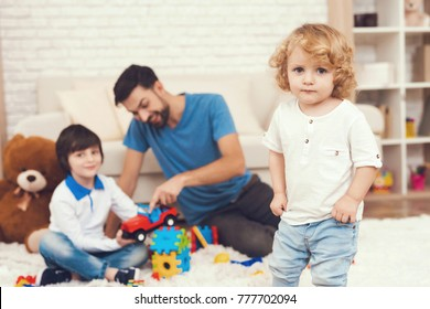 A man spends time with his sons. The father of two boys is engaged in raising children. Father plays games with boys.