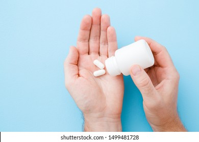 Man spilling out white pills from bottle in his hand. Receiving vitamins or medicaments. Men's issues. Medical, pharmacy and healthcare concept. Point of view shot. Close up. Pastel blue background.