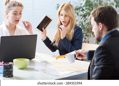 Man spilling tea on documents at work