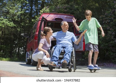 Man with spinal cord injury in a wheelchair with family near his adaptive van with teenager on a skateboard