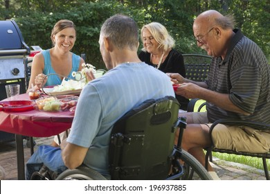 Man with spinal cord injury in wheelchair at family outdoor cookout picnic