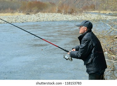 A man with spinning rod on fishing.