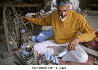 man spinning the wheel at factory, delhi, india